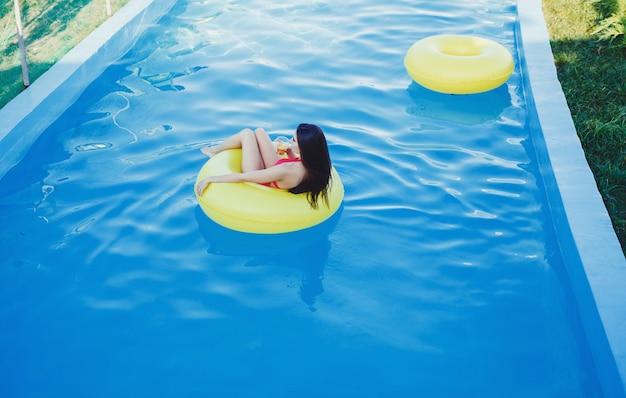 Fille flottant sur un matelas de plage Photo Premium