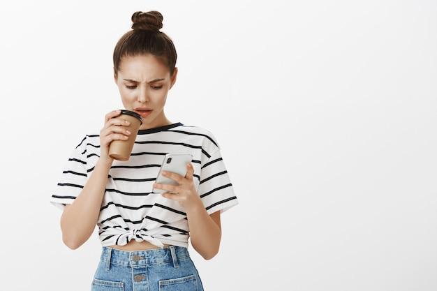 Fille Fronçant Les Sourcils Confus Regardant L'écran Du Téléphone Mobile Tout En Faisant Une Gorgée De Café à Partir D'une Tasse Photo gratuit