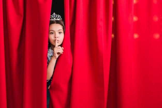 Fille furtivement du rideau rouge faisant un geste silencieux Photo gratuit