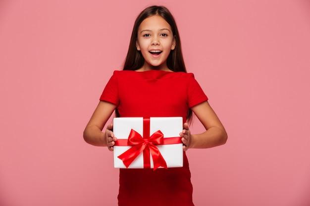 Fille Gaie Montrant Un Cadeau Et Souriant Isolé Sur Rose Photo gratuit