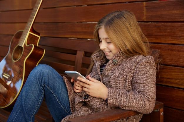 Fille de gamin blond jouant smartphone Photo Premium