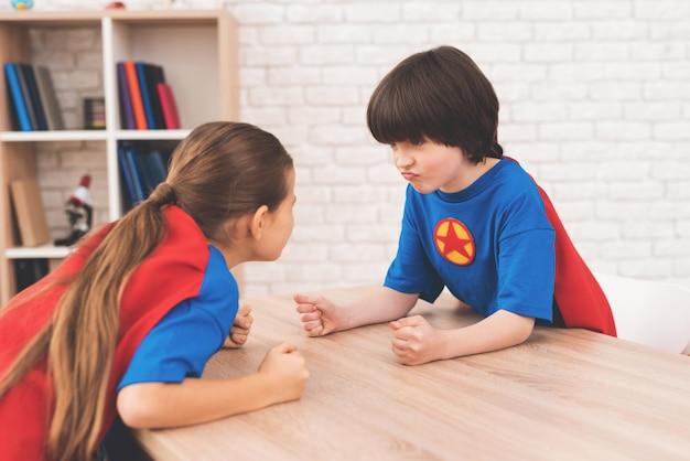 Une fille et un garçon mesurent leur force dans une pièce lumineuse. Photo Premium