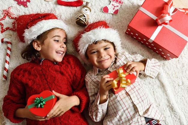 Fille et garçon portant le chapeau de santa Photo gratuit