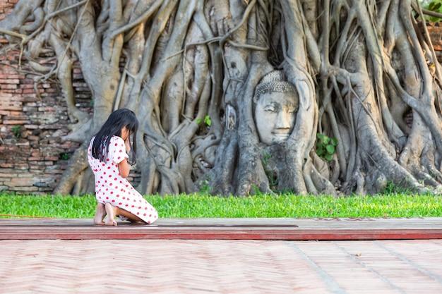 Une Fille à Genoux Prier Pour Saint à La Tête De La Statue De Bouddha Dans Les Racines Des Arbres Au Wat Mahathat Dans La Province D'ayutthaya, Thaïlande Photo Premium
