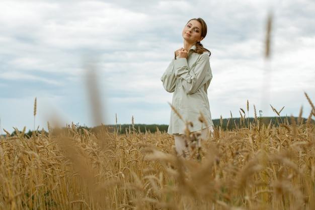Fille Gentille Et Douce Dans Des Vêtements Légers, Debout Au Milieu Du Champ. Photo Premium