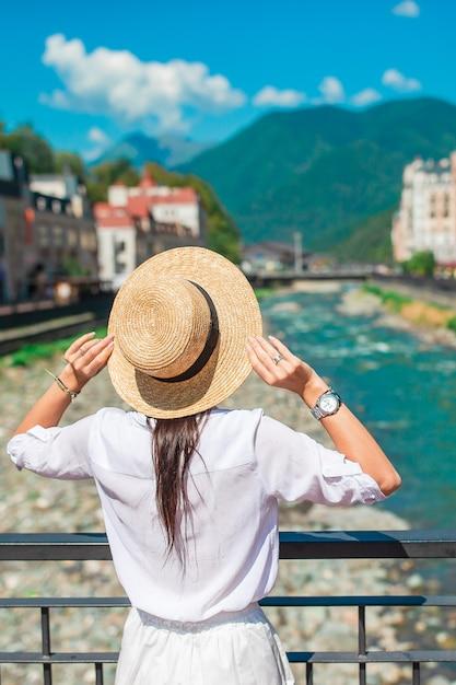 Fille heureuse au chapeau sur le quai d'une rivière de montagne dans une ville européenne. Photo Premium