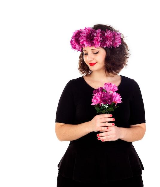 Fille heureuse avec une branche et une couronne avec des fleurs roses et violettes Photo Premium