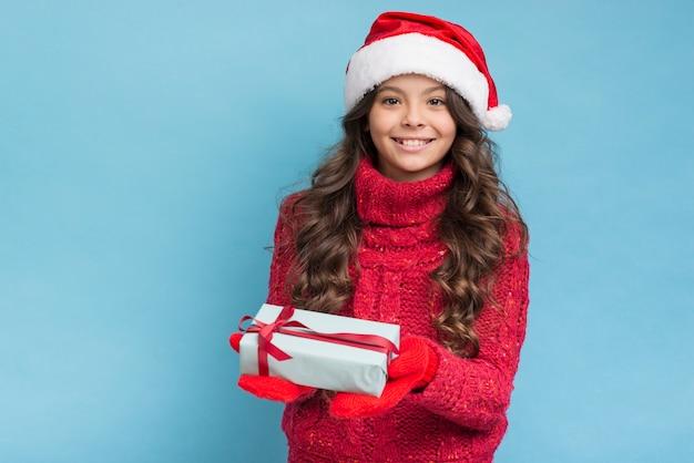 Fille heureuse avec un cadeau dans ses mains Photo gratuit