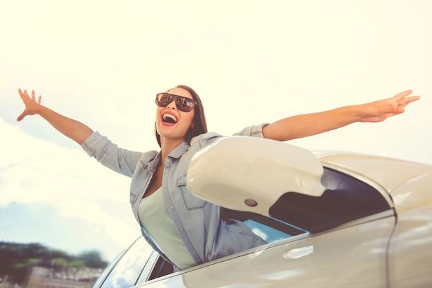 Fille heureuse dans des vêtements élégants et des lunettes de soleil Photo Premium