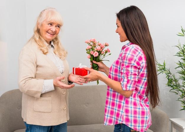 Fille Heureuse Donnant Un Coffret Cadeau Et Un Bouquet De Fleurs à Sa Mère Photo gratuit