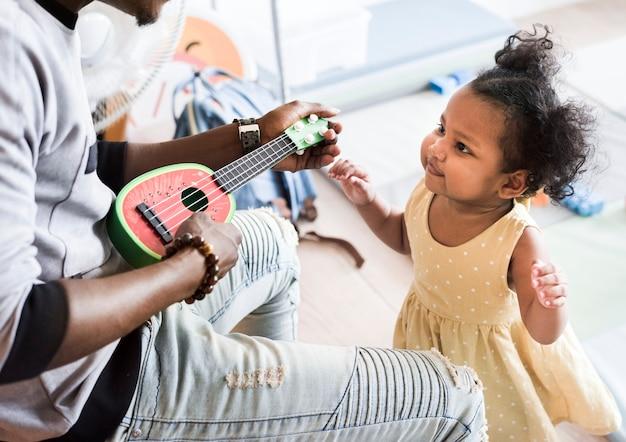 Fille heureuse et enseignant s'amuser dans une crèche Photo Premium