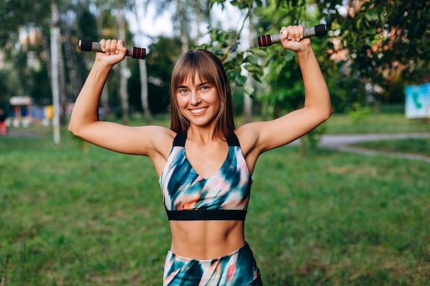 Fille heureuse faisant des exercices avec des haltères en plein air Photo Premium