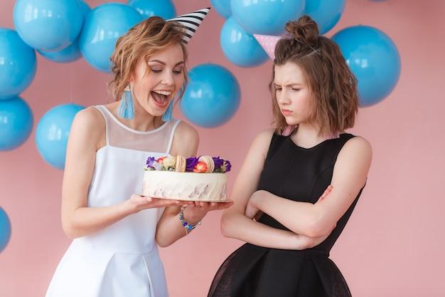 Fille heureuse et fille triste à la recherche d'un gâteau d'anniversaire. concept de dualité Photo gratuit
