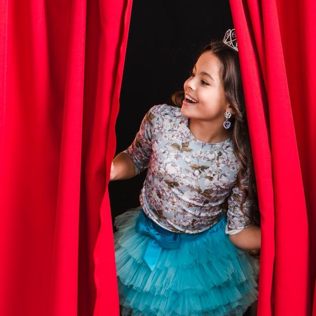 Fille heureuse furtivement du rideau rouge sur scène Photo gratuit