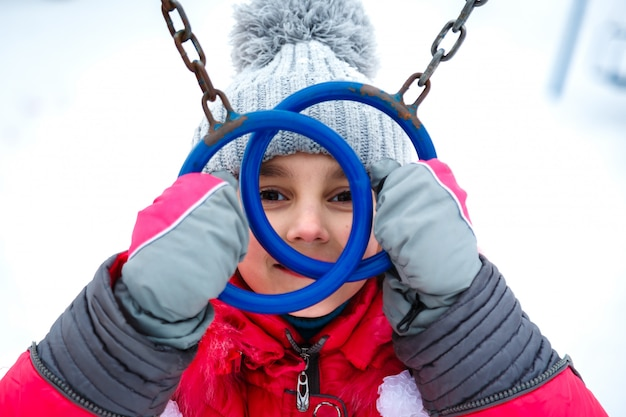 Fille heureuse jouant sur un terrain de jeu au jour glacial d'hiver. Photo Premium