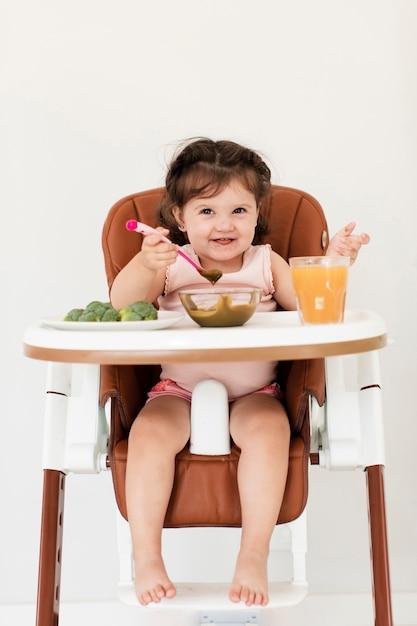 Fille heureuse mangeant dans une chaise d'enfant Photo gratuit