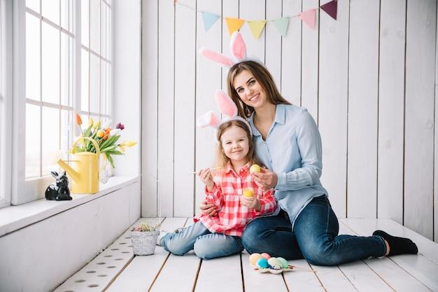 Fille heureuse et mère dans les oreilles de lapin peignant des oeufs pour pâques Photo gratuit