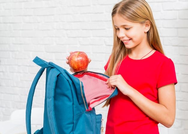 Fille heureuse mettant la pomme dans le sac à dos Photo gratuit