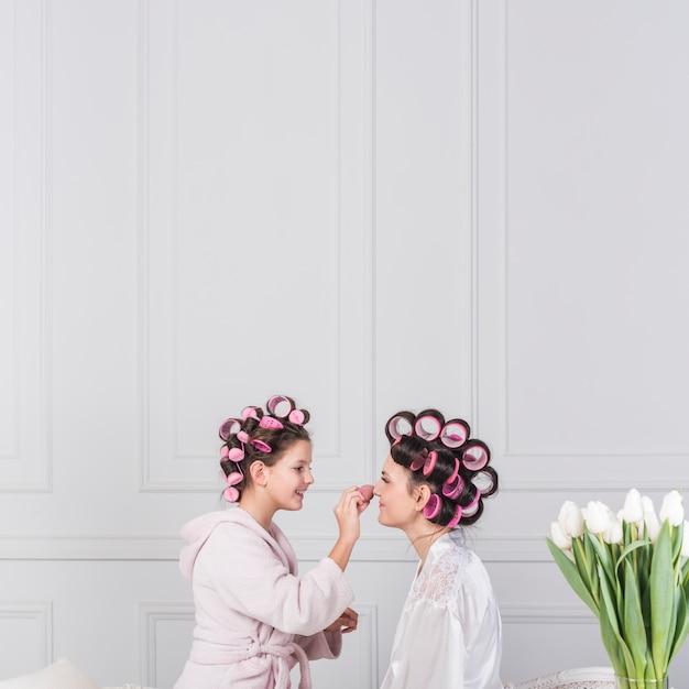 Fille Heureuse Mettant La Poudre Sur Le Visage Des Mères Photo gratuit