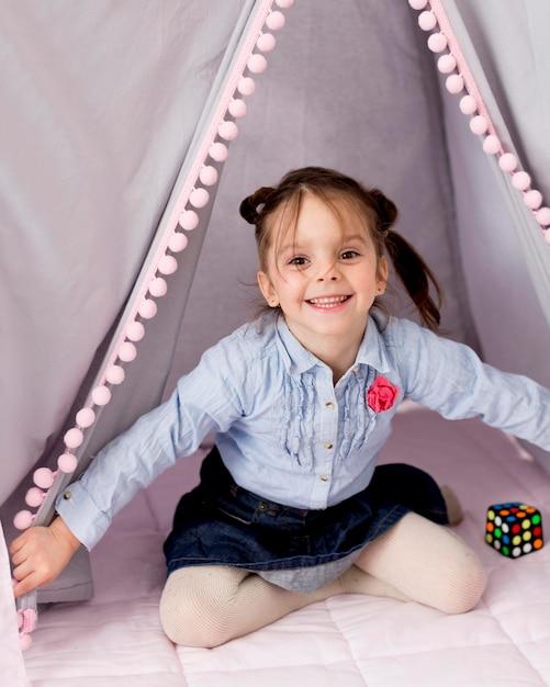 Fille Heureuse Posant Sous Tente à La Maison Photo gratuit