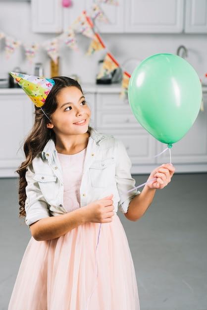 Fille heureuse en regardant ballon vert dans la cuisine Photo gratuit