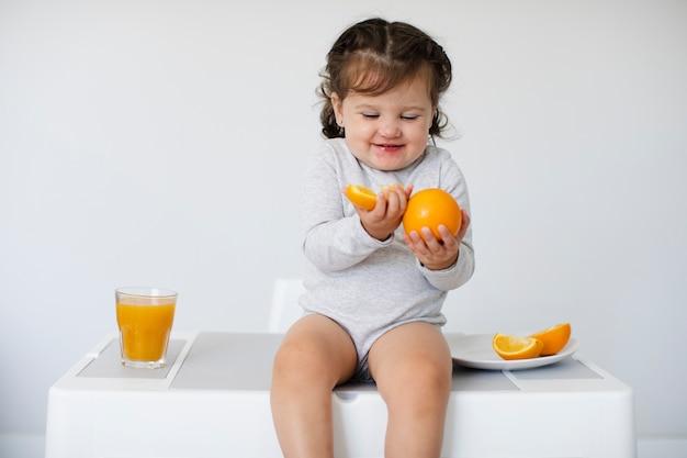 Fille Heureuse En Regardant Ses Oranges Photo gratuit