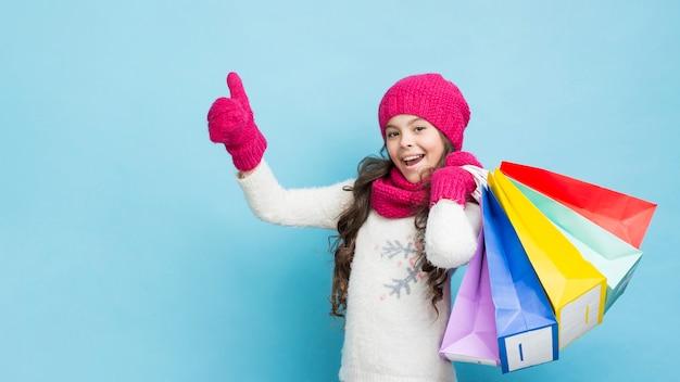 Fille heureuse avec des sacs de vêtements d'hiver Photo gratuit