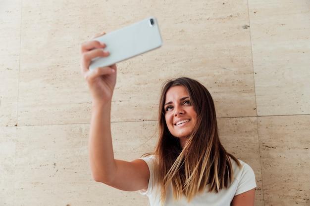 Fille heureuse avec téléphone prenant un selfie Photo gratuit