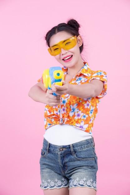 Fille heureuse tenant un pistolet à eau de fond rose. Photo gratuit