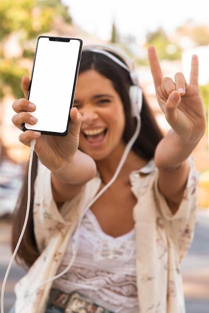Fille Heureuse De Tir Moyen Avec Smartphone Photo gratuit