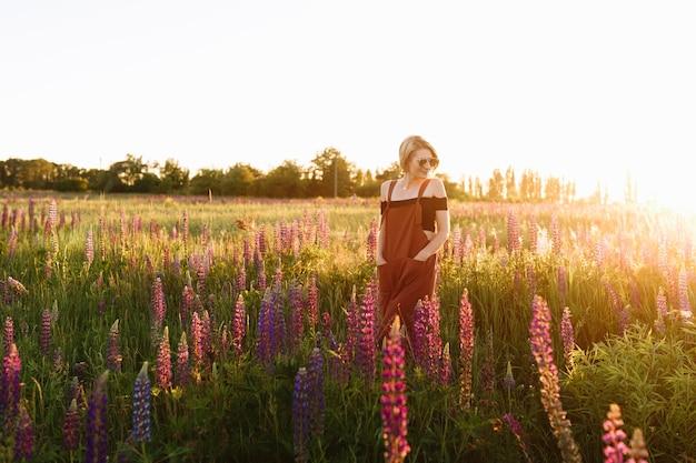 Fille de hipster moderne marchant dans le champ de fleurs sauvages au coucher du soleil. Photo gratuit
