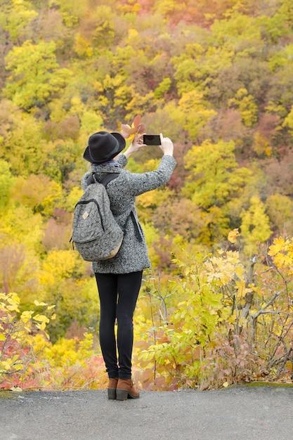 Fille Avec Des Images De Téléphone Portable De La Forêt D'automne. Vue Arrière Photo Premium