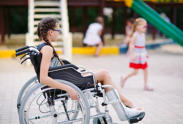 Une Fille Avec Une Jambe Cassée Est Assise Dans Un Fauteuil Roulant Devant Le Terrain De Jeu. Photo Premium