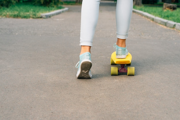 Fille en jeans et baskets faisant du skateboard dans le parc Photo Premium