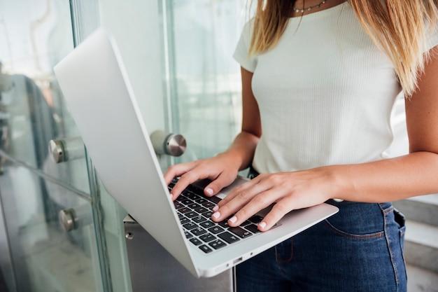 Fille en jeans touchant le clavier d'ordinateur portable Photo gratuit
