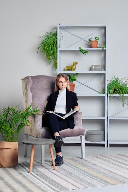 Fille en jeans et veste assis dans le salon avec le magazine Photo Premium