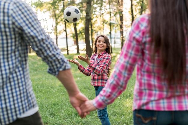 Fille jouant avec un ballon de soccer devant les parents se tenant la main dans le parc Photo gratuit