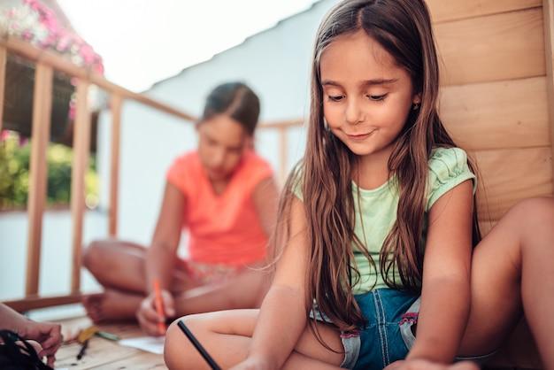 Fille jouant dans la cabane avec des amis et dessinant aux crayons de couleur Photo Premium