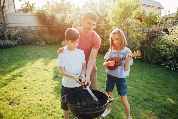 Fille jouant du ukulélé debout près de son père et de son frère, préparant un repas sur le barbecue Photo gratuit