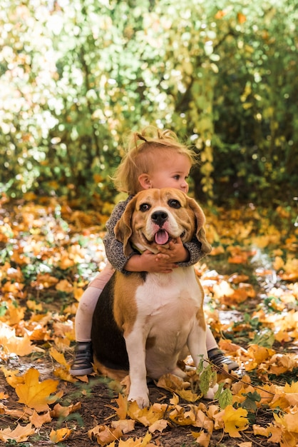 Fille jouant avec son animal de compagnie en forêt Photo gratuit