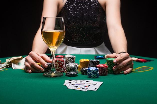 Une fille joue au poker dans un casino avec des jetons, des dollars et du vin Photo Premium