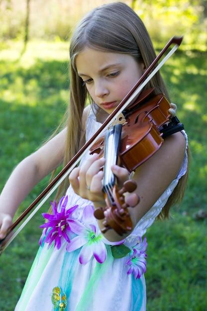 Fille joue du violon à l'extérieur Photo Premium