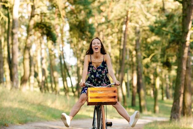 La fille joue le fou sur le vélo. Photo gratuit