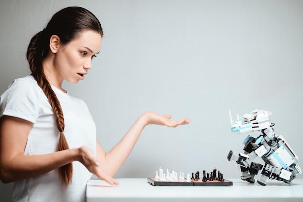 Une fille joue avec un robot aux échecs. Photo Premium