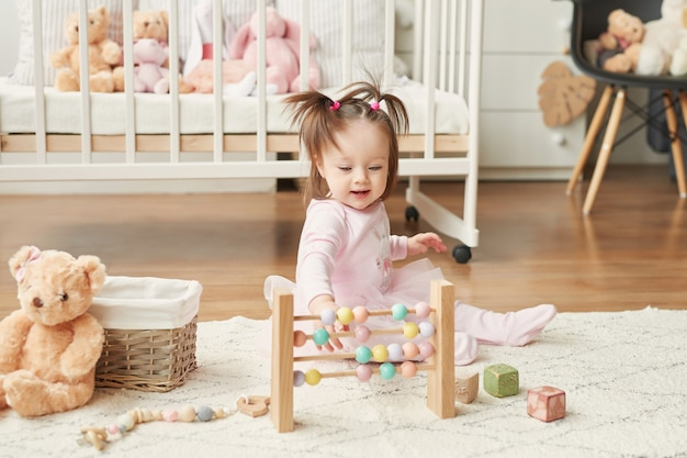 Fille avec des jouets dans la chambre des enfants Photo Premium