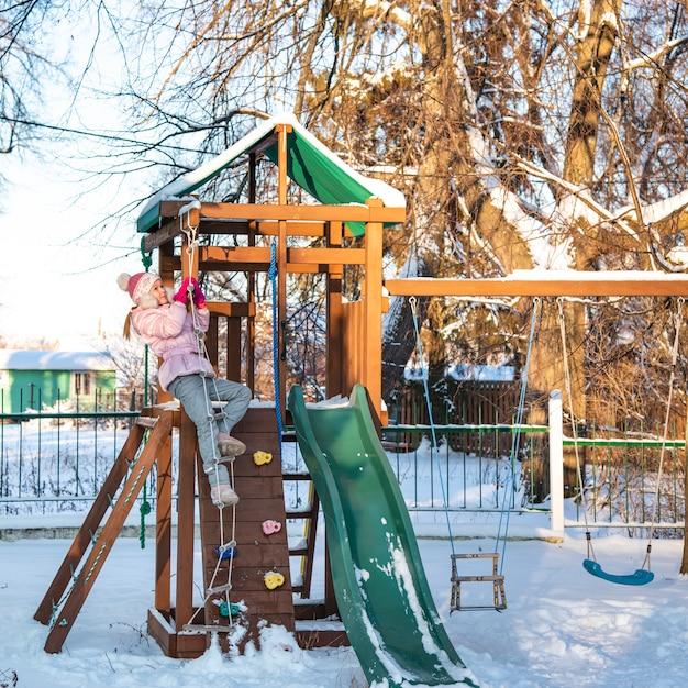 Une fille joyeuse enfant jouant sur le terrain de jeu en journée ensoleillée d'hiver enneigé. Photo Premium