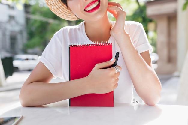 Fille Joyeuse Excitée Avec Livre De Planificateur Rouge Se Détendre Dans Un Café En Plein Air Le Matin D'été, Créant De La Poésie Pendant Le Déjeuner Photo gratuit