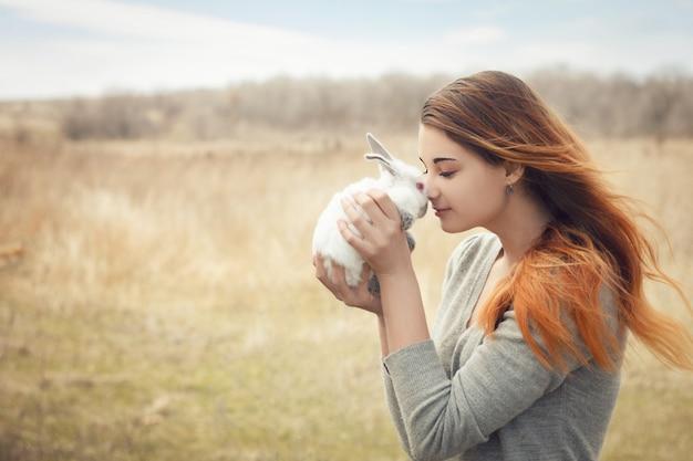 La fille avec le lapin. heureuse petite fille tenant un joli lapin moelleux Photo Premium