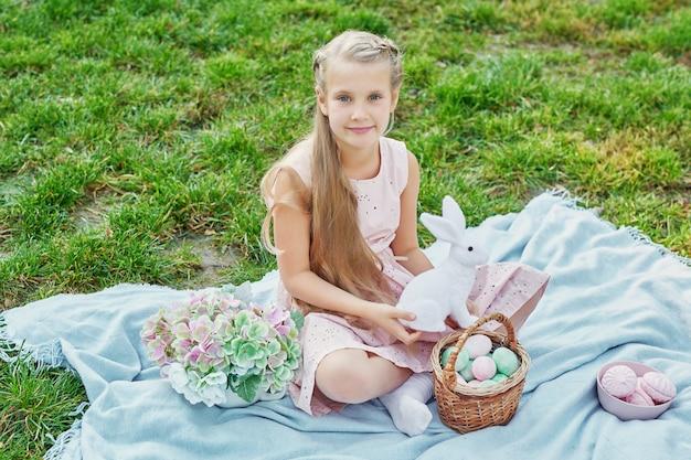 Fille Avec Lapin Et Oeufs Pour Pâques Dans Le Parc Sur L'herbe Verte Photo Premium