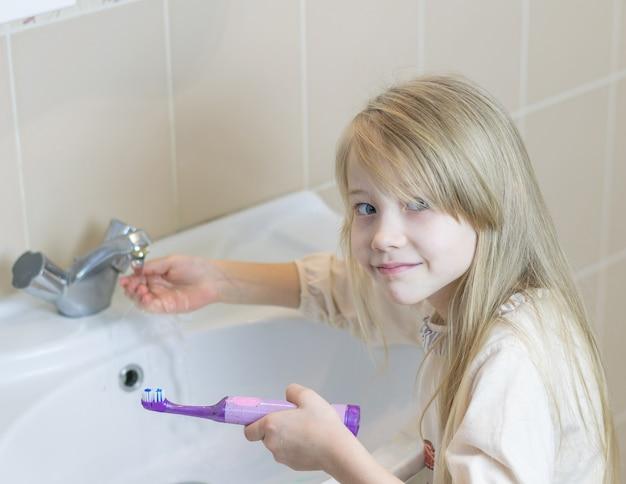 Une fille lave une brosse à dents électrique dans la salle de bain. Photo Premium